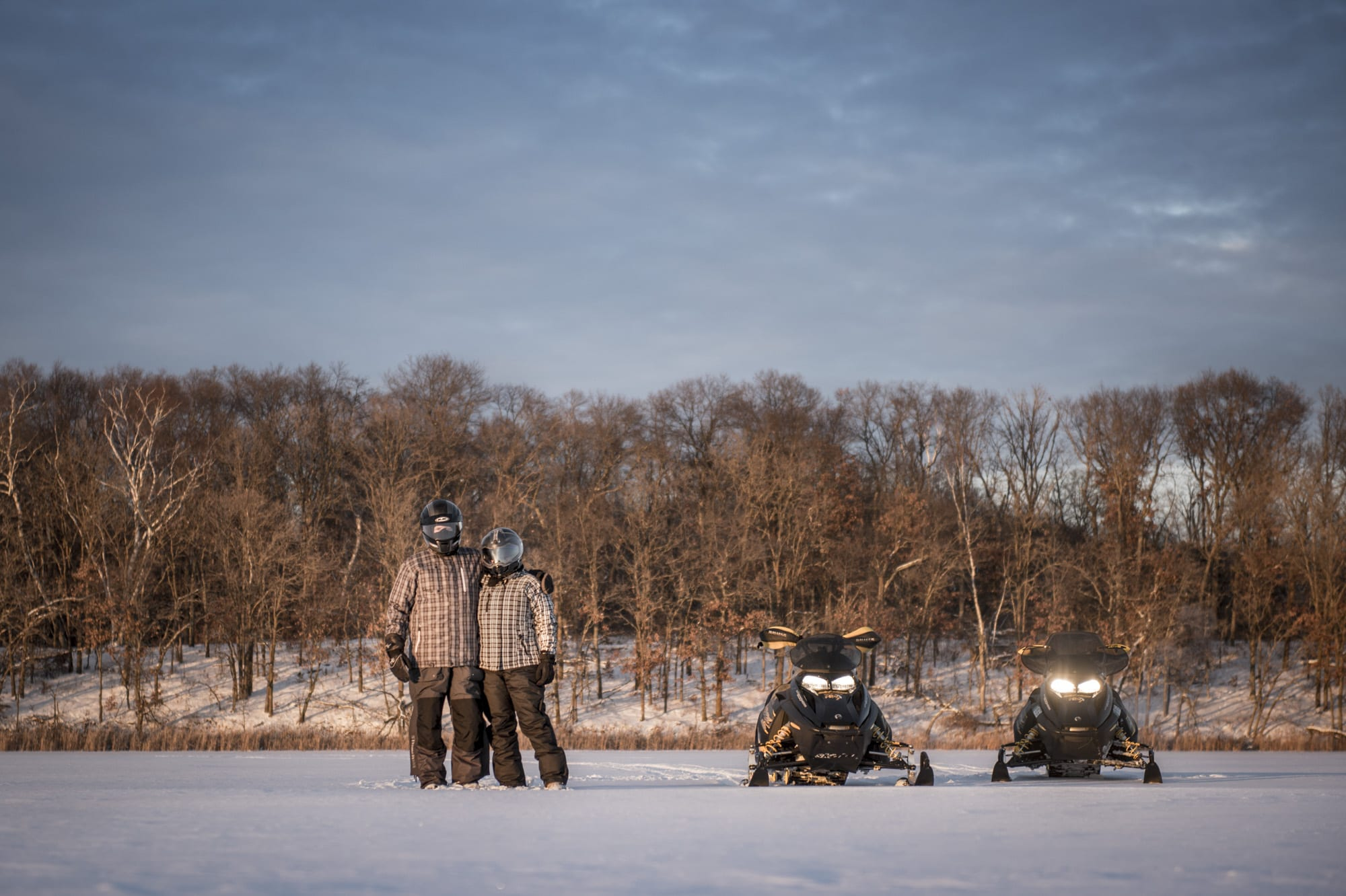 Two people posing on frozen lake near snowmobiles.