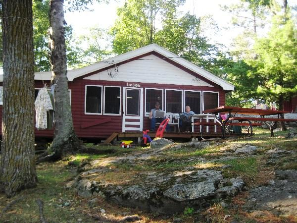 People sitting on porch of cabin.