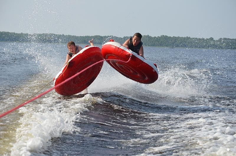 Two kids on two airborne tubes pulled behind boat.