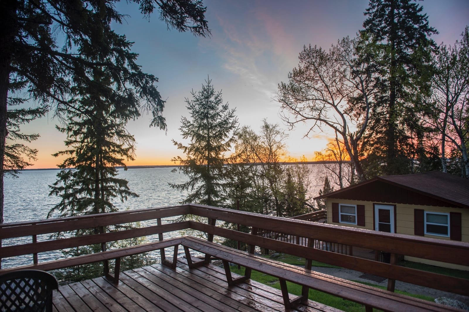 Wooden deck overlooking lake at sunset.