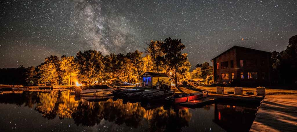 Resort docks and cabins at night under stars.