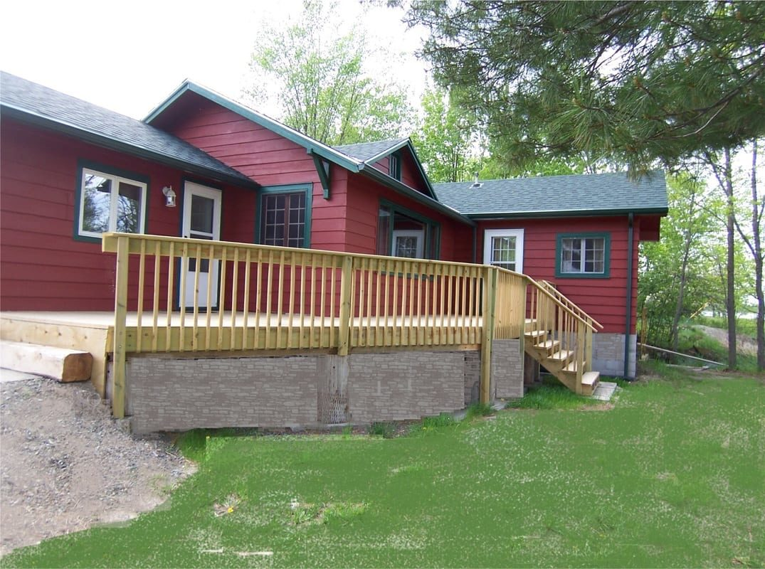 Red resort cabin with green trim and wooden porch.