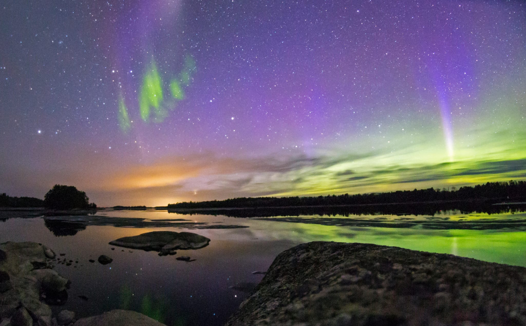 Northern lights over calm lake.