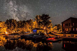 Resort docks and cabins at night under stars.